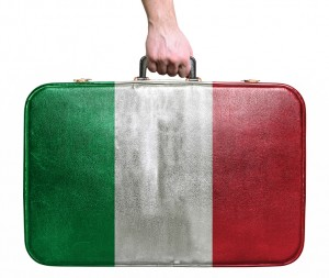 Tourist hand holding vintage leather travel bag with flag of Italy